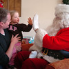 Bal Swan Children's Center student Lydia Triplett, 3, center, with her father Matt, gives Santa a high five after receiving a gift from Santa at the Louisville Elk's Lodge for the Santa Run on Saturday.<br /> For more photos please see broomfieldenterprise.com.<br /> December 3, 2011<br /> staff photo/ David R. Jennings