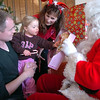 Bal Swan Children's Center student Lydia Triplett, 3, center, with her father Matt, receives a gift from Santa with Santa's helper Patty Ferguson at the Louisville Elk's Lodge for the Santa Run on Saturday.<br /> For more photos please see broomfieldenterprise.com.<br /> December 3, 2011<br /> staff photo/ David R. Jennings