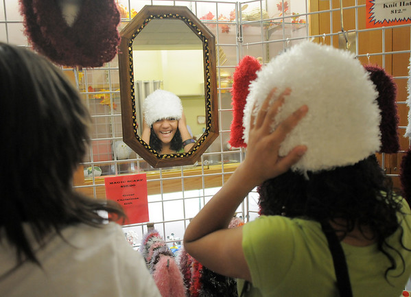 Sabrena Quinlan, 13, right, tries on a hat with her friend Meaghan Fenton, 14, at a booth during Saturday's Santa's Cellar Craft Fair at the Broomfield Community Center.<br /> <br /> November 11, 2011<br /> staff photo/ David R. Jennings