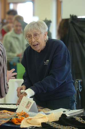 Doris Sauerland shows a customer her knitted wrist warmers during Saturday's Santa's Cellar Craft Fair at the Broomfield Community Center.<br /> <br /> November 11, 2011<br /> staff photo/ David R. Jennings