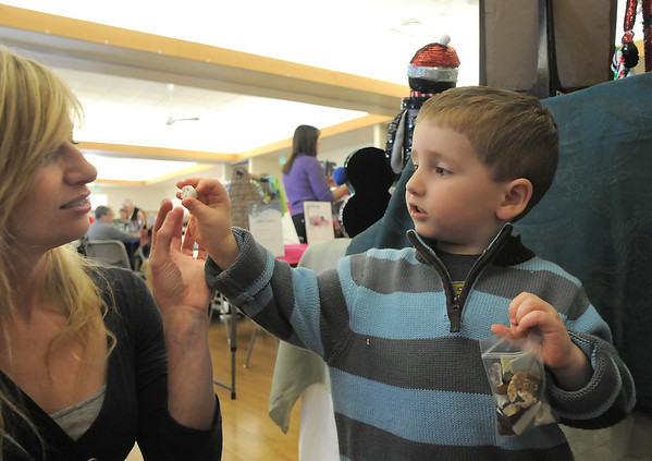 Nicholas Cianciolo, 3, shows his mother, Mary, a rock he likes for his bag of rocks during Saturday's Santa's Cellar Craft Fair at the Broomfield Community Center.<br /> <br /> November 11, 2011<br /> staff photo/ David R. Jennings