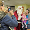 Julie Sturtz and her daughter Molly, 2, pose for a picture with Santa Claus taken by their friend Wyndy Flato, left, during Saturday's Santa's Cellar Craft Fair at the Broomfield Community Center.<br /> <br /> November 11, 2011<br /> staff photo/ David R. Jennings