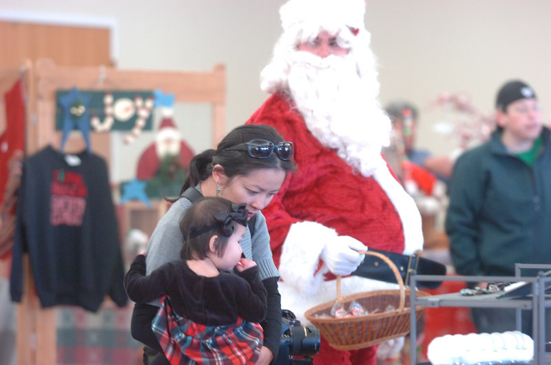 Angie Nguyen and her daughter Wren, 17 months-old, look at items for sale while Santa Claus waits to hand out candy during Saturday's Santa's Cellar Craft Fair at the Broomfield Community Center.<br /> <br /> November 11, 2011<br /> staff photo/ David R. Jennings