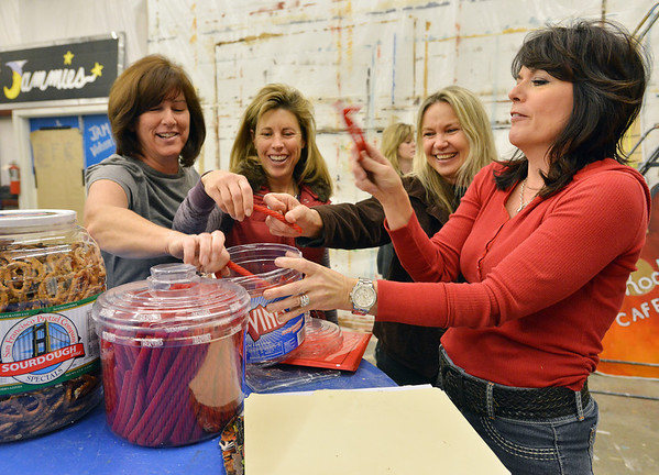 Judy Witt, left, Steffanie Frese, Tess LeBlanc and Rachelle Moschette give each other a toast with liquorice during a break in working on  Broomfield High School's Just After Midnight after prom event in the JAM Shed at Broomfield High on Saturday.<br /> January 26, 2013<br /> staff photo/ David R. Jennings