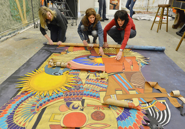 Tammy Degenhart, left, Kim Harrison with Rock Canyon High, and Rachelle Moschetti roll up a Egyptian themed murals in the JAM Shed at Broomfield High on Saturday.<br /> January 26, 2013<br /> staff photo/ David R. Jennings