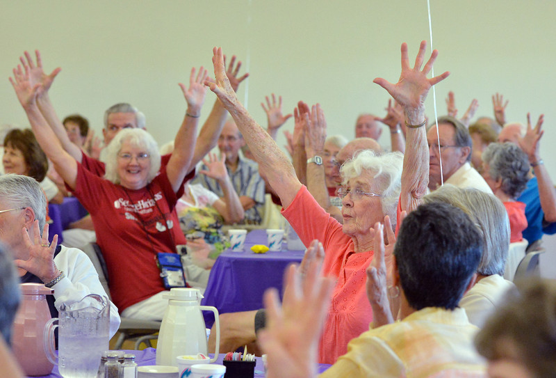 Silver Sneakers 10th Anniversary celebrants raise their arms for a stretch before getting their food at the Broomfield Community Center on Friday.<br /> <br /> July 20, 2012<br /> staff photo/ David R. Jennings