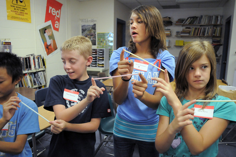 Kevin Truong, left, Ryan Gilpatrick, 8th grader Devan DeFreece and Dione Horne touch straws together with their fingers while standing in a circle for a getting acquainted game during Westlake Middle School's 6th grade orientation on Thursday.<br /> August 11, 2011<br /> staff photo/ David R. Jennings