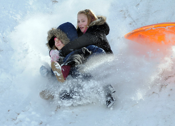 "Makenna Wagner, 10, left, and Kaylie Hayes, 12, slide down ""hospital hill"" after loosing their sled on Saturday near Oak Circle and Miramonte Blvd.<br /> February 4, 2012<br /> staff photo/ David R. Jennings"