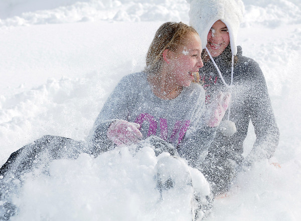 "Kaylie Hayes, 12, front, and Maddie Wagner, 11, get show in their faces as they slide down ""hospital hill"" near Oak Circle and Miramonte Blvd. on Saturday.<br /> February 4, 2012<br /> staff photo/ David R. Jennings"