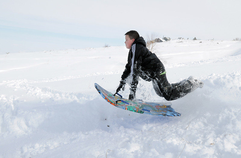 """Grant Misztal, 11, gets some air while sledding down """"hospital hill"""" near Oak Circle and Miramonte Blvd. on Saturday.<br /> February 4, 2012<br /> staff photo/ David R. Jennings"""