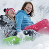 "Makenna Wagner, 10, left, and Maci Triezenberg, 11, laugh as they slide down ""hospital hill"" near Oak Circle and Miramonte Blvd. on Saturday.<br /> February 4, 2012<br /> staff photo/ David R. Jennings"