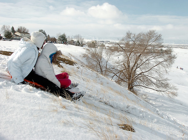 "Maddie Wagner, 11, left, and Maci Triezenberg, 11, start their sledding run down ""hospital hill"" near Oak Circle and Miramonte Blvd. on Saturday.<br /> February 4, 2012<br /> staff photo/ David R. Jennings"