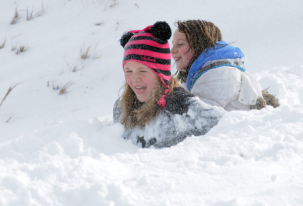 "Makenna Wagner, 10, left, and Maci Triezenberg, 11, are buried above their waists after sliding down ""hospital Hill"" near Oak Circle and Miramonte Blvd. on Saturday.<br /> February 4, 2012<br /> staff photo/ David R. Jennings"