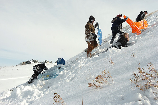 "Sledders make the hike to the top of ""hospital hill"" near Oak Circle and Miramonte Blvd. on Saturday.<br /> February 4, 2012<br /> staff photo/ David R. Jennings"
