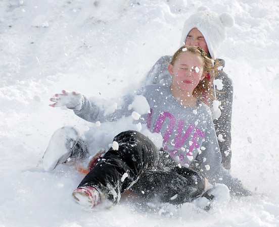 "Kaylie Hayes, 12, left, and Maddie Wagner, 11, catch snow in their faces as they slide down ""hospital hill"" near Oak Circle and Miramonte Blvd. on Saturday.<br /> February 4, 2012<br /> staff photo/ David R. Jennings"