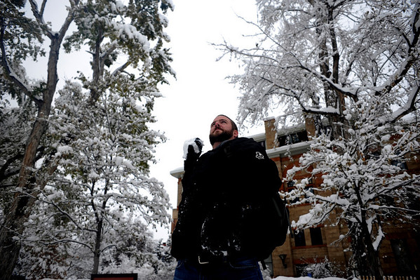 Junior Nate Artist molds a snowball to throw at a snow-covered tree on Norlin Quad on the University of Colorado campus in Boulder, Thursday, Oct. 29th, 2009. Boulder saw 17 inches by Thursday morning, and expected up to 10 more inches by the end of the day.  <br /> KASIA BROUSSALIAN / THE CAMERA