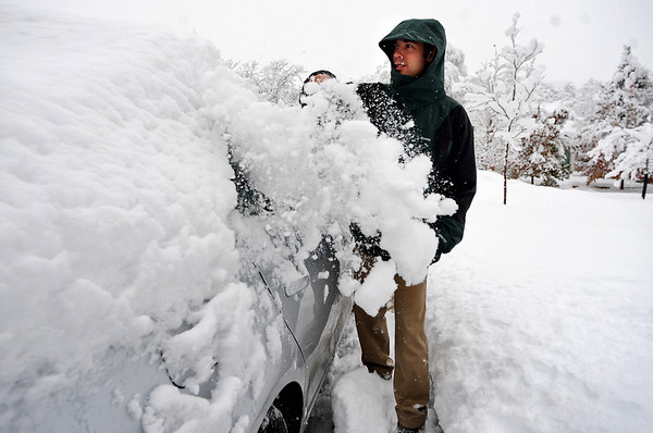 SNOW104<br /> Daniel Wells clears off his car before heading to work at the Rio Grande on Thursday morning.<br /> Photo by Marty Caivano/Camera/Oct. 29, 2009