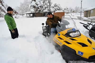 SNOW106 Matt Muir, left, and Scott Raderstorf, volunteers with Boulder Nordic Sport, prepare their snowmobile and grooming apparatus at North Boulder Park on Thursday. Photo by Marty Caivano/Camera/Oct. 29, 2009