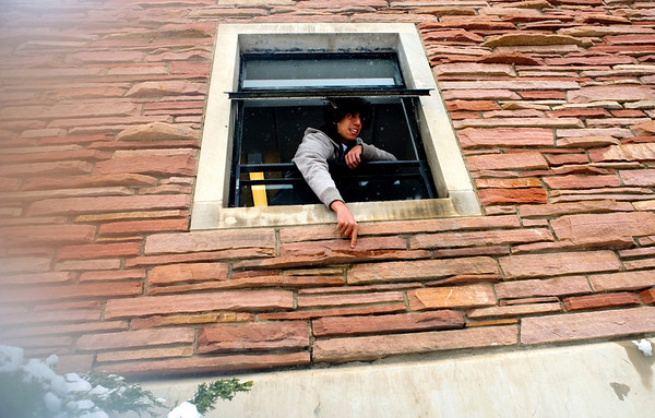 Freshman Alex Leonard hangs out his window at Libby dormitories as snow falls on the University of Colorado campus in Boulder, Thursday, Oct. 29th, 2009. Boulder saw 17 inches by Thursday morning, and expected up to 10 more inches by the end of the day.  <br /> KASIA BROUSSALIAN / THE CAMERA