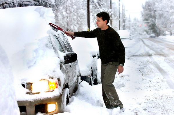 Peter Zaidel braves the early morning chill in Lafayette to clean off his car Thursday morning.<br /> Photo by Paul Aiken The Camera Oct 29 2009