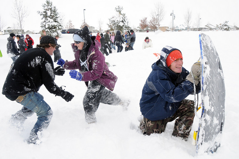 Jacob Stauf, 15, right,  holds a sled for a shield as Dan Leurck, 15, is attacked by Danica Spicer, 16, after advancing on the other team during the snowball fight organized by Broomfield High School students at the Broomfield County Commons on Thursday<br /> <br /> October 29, 2009<br /> Staff photo/David R. Jennings