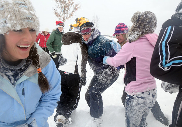 Marc Besson, 16, is attacked by a group of girls trying to get him down in the snow during the snowball fight organized by Broomfield High School students at the Broomfield County Commons on Thursday. Brittney Zec, 15, is at left.<br /> <br /> October 29, 2009<br /> Staff photo/David R. Jennings