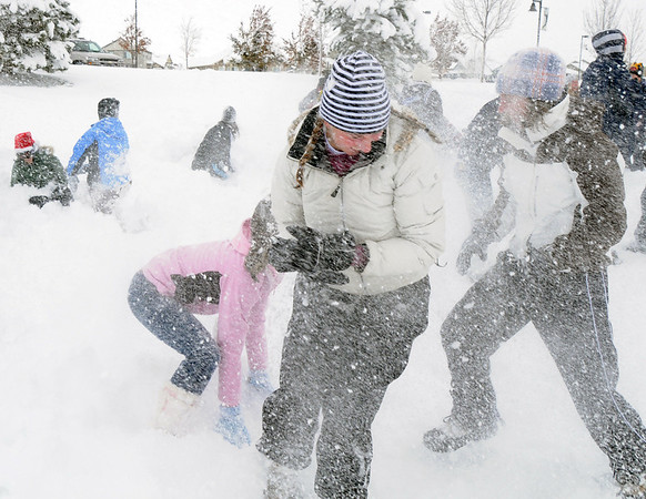 Elizabeth Belton, 16, center, is pelted by snowballs during the snowball fight organized by Broomfield High School students at the Broomfield County Commons on Thursday<br /> <br /> October 29, 2009<br /> Staff photo/David R. Jennings