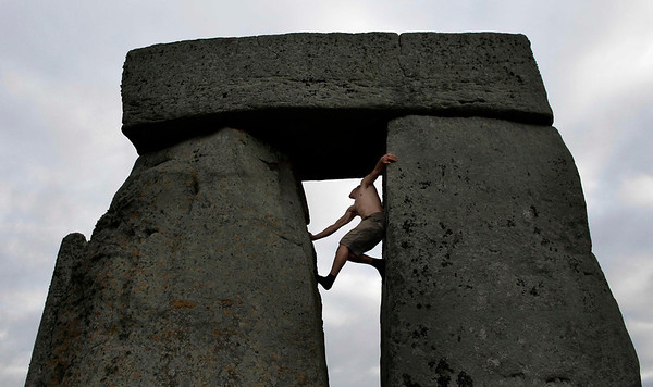 Britain Stonehenge .JPEG-08.JPG A reveller climbs stones during the summer solstice at Stonehenge, near Salisbury in England, Tuesday, June 21, 2011.  The ancient stone circle of Stonehenge is a World Heritage Site erected between approximately 3000BC and 1600BC and despite years of research the reason behind its construction remains a mystery. The summer solstice in the northern hemisphere occurs annually on June 21 and is the time at which the sun is at its northernmost point in the sky.  (AP Photo/Matt Dunham)