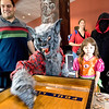 Gabriel Negron, age 8, plays shuffleboard for candy while dad Charles, left and sister Rachel, age 7, look on during the Spooktacular event at the Broomfield First Bank Center on Saturday. Liam Negron, age 12, is dressed as the Grim Reaper, right. <br /> <br /> photo/Matt Kelley