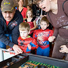 Jay Stone, age 4, tries his luck at the giant pin-ball game while dad, Mark,left, brother John, age 5 and Mom Jana cheer him on during the Spooktacular event at the Broomfield First Bank Center on Saturday. <br /> <br /> photo/ Matt Kelley