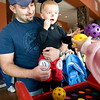 Sean Koon holds his son Caden, age 1, for a whiffle-ball toss attempt during the Spooktacular event at the Broomfield First Bank Center on Saturday.<br /> <br /> photo/ Matt Kelley