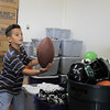 Omar Delgado, 8, plays with a football while looking through donated sporting goods equipment at A Precious Child on Thursday.<br /> <br /> July 7, 2011<br /> staff photo/ David R. Jennings