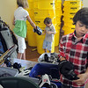 Dan White, 8, right, tries on a glove while his siblings London, 11, left, and William, 4,  play with some of the  donated sporting equipment at A Precious Child on Thursday.<br /> <br /> July 7, 2011<br /> staff photo/ David R. Jennings