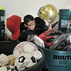 Dax White, 8, looks at a helmet while sorting through donated sporting equipment at A Precious Child on Thursday.<br /> <br /> July 7, 2011<br /> staff photo/ David R. Jennings