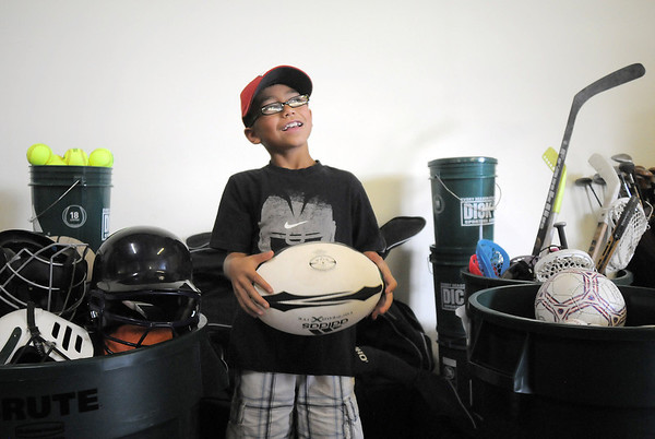 Dax White, 8, holds a rugby ball while sorting through donated sporting equipment at A Precious Child on Thursday.<br /> <br /> July 7, 2011<br /> staff photo/ David R. Jennings