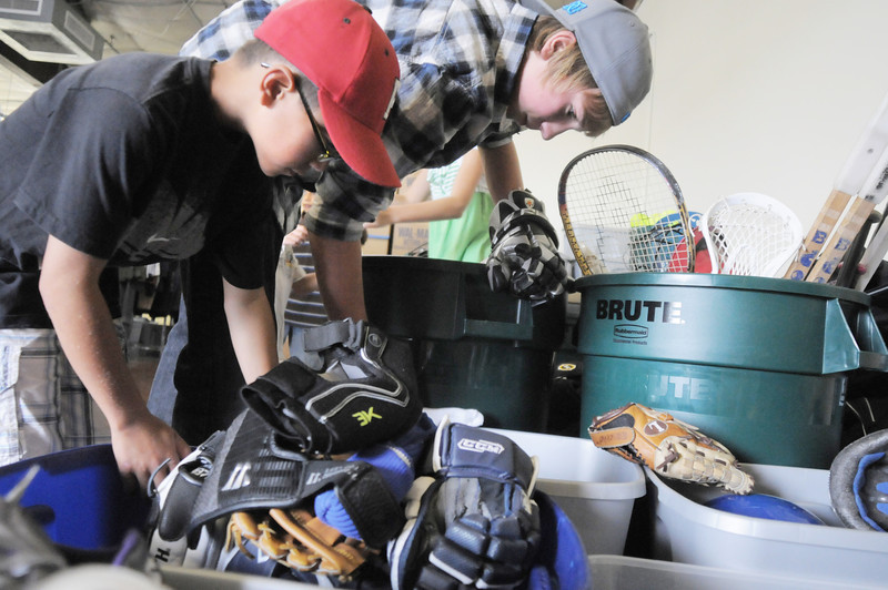 Dax White , 8, left, and his brother Leif, 13, look for gloves in the  donated sporting goods equipment at A Precious Child on Thursday.<br /> <br /> July 7, 2011<br /> staff photo/ David R. Jennings