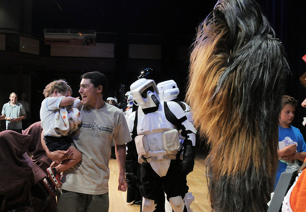 Joel Ezell laughs as his sonZachary, 2, plays peek -a-boo with a Wookie portrayed by a member of the Rebel Legion during the Star Wars fundraiser for the Broomfield Public Library Foundation on Sunday at the Audi. <br /> <br /> August 7, 2011<br /> staff photo/ David R. Jennings