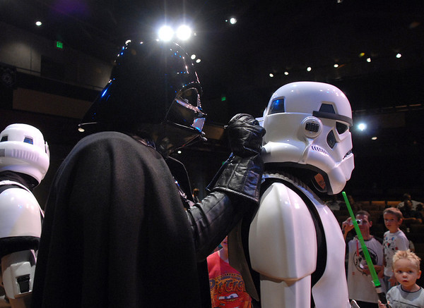 Darth Vader uses a soldier as a table to sign an autograph at the Star Wars fundraiser for the Broomfield Public Library Foundation on Sunday at the Audi. <br /> <br /> August 7, 2011<br /> staff photo/ David R. Jennings