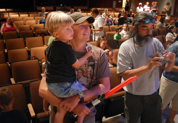 Mike Hyten hods his son Charlie, 3 1/2, in his arms as they watch members of the Rebel Legion and 501st Legion Mountain Garrison dressed in costume on stage at the Audi during the Star Wars fundraiser for the Broomfield Public Library Foundation on Sunday. <br /> <br /> August 7, 2011<br /> staff photo/ David R. Jennings
