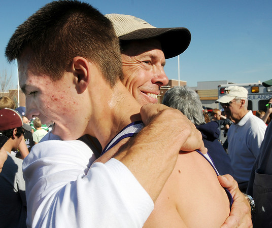 Holy Family's head coach Dave Good, right, hugs Sean Ankarlo after finishing his race at the state cross country meet at Fossil Ridge High School in Ft. Collins on Saturday.<br /> <br /> November 7, 2009<br /> Staff photo/David R. Jennings