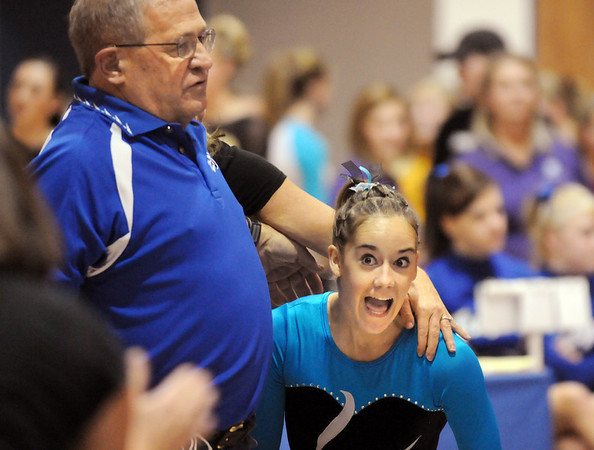 JoJo Hayden, right, gives a cheer while standing next to assistant coach Bob Prince, after performing her floor routine during the state 5A gymnatics meet at Thornton High School on Friday.<br /> <br /> November 6, 2009<br /> Staff photo/David R. Jennings