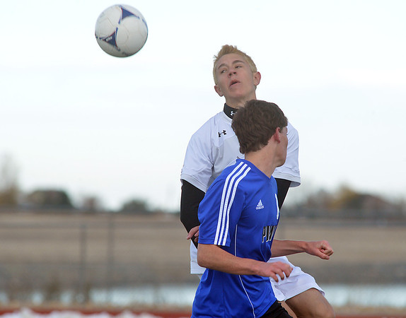Holy Family's Matt O'Hayre does a header against  Peak to Peak's Moritz Zerwes during Saturday's state playoff game at Mike G. Gabriel Stadium.<br /> October 25, 2012<br /> staff photo/ David R. Jennings