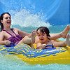 "Kirsten Beemer, left, lands in the pool with her son Koen, 10, after going down the big blue slide while enjoying the fun  and sun at The Bay Aquatic Center on Saturday.<br /> <br /> June 30, 2012<br /> staff photo/ David R. Jennings<br /> <br /> for more photos please go to  <a href=""http://www.broomfieldenterprise.com"">http://www.broomfieldenterprise.com</a>"