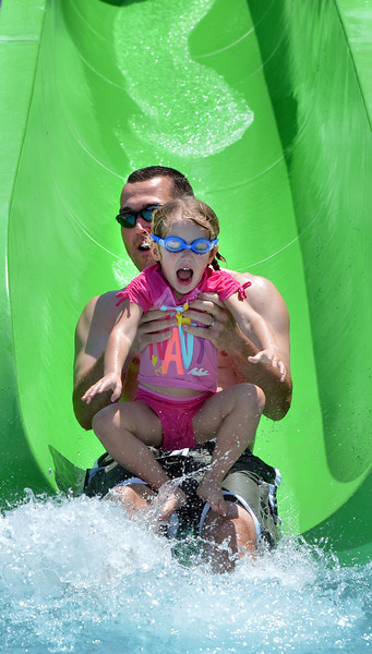 "Mike Ramey holds his daughter Payton, 3, as they hit the water at the end of the green slide while enjoying the fun and sun at The Bay Aquatic Center on Saturday.<br /> <br /> June 30, 2012<br /> staff photo/ David R. Jennings<br /> <br /> for more photos please go to  <a href=""http://www.broomfieldenterprise.com"">http://www.broomfieldenterprise.com</a>"