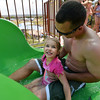 "Payton Ramey, 3, looks at her father Mike as they get ready to go down the green slide while enjoying the fun at The Bay Aquatic Center on Saturday.<br /> <br /> June 30, 2012<br /> staff photo/ David R. Jennings<br /> <br /> for more photos please go to  <a href=""http://www.broomfieldenterprise.com"">http://www.broomfieldenterprise.com</a>"