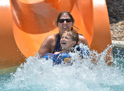Allison Patrick and her son Cater, 4, make a big splash after going down the orange slide while cooling off from the heat and enjoying the fun at The Bay Aquatic Center on Saturday.  June 30, 2012 staff photo/ David R. Jennings  for more photos please go to www.broomfieldenterprise.com