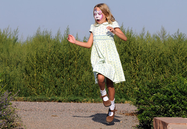 Ella Schigur, 8, skips around the garden area waiting for the concert to begin during Sunday's Summer Sundays Finale Carnival and Concert for the Broomfield Council on the Arts and Humanities at the Brunner House.<br /> <br /> August 9, 2009<br /> staff photo/David R. Jennings