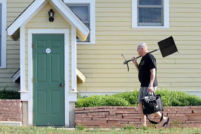 Jim Mick, director of the Metropolitan Jazz Orchestra, carries his music stand for a concert during Sunday's Summer Sundays Finale Carnival and Concert for the Broomfield Council on the Arts and Humanities at the Brunner House.  August 9, 2009 staff photo/David R. Jennings