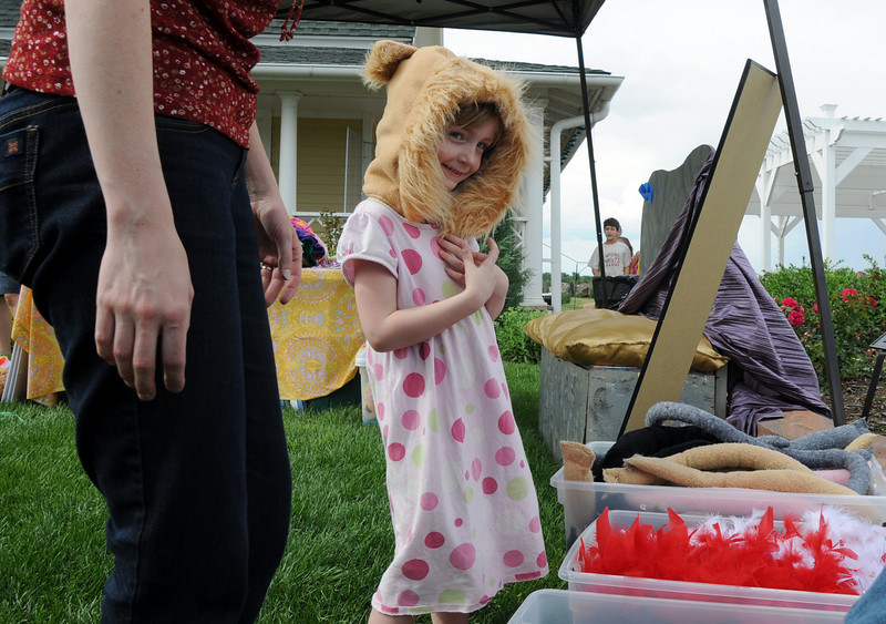 Emily Kirk, 5, tries on her lion costume for the play the lion and the mouse at the Backstory Theater booth during the Broomfield Council on the Arts and Humanities Summer Sundays at the Brunner <br /> Farmhouse.<br /> <br /> July 11, 2010<br /> Staff photo/ David R. Jennings
