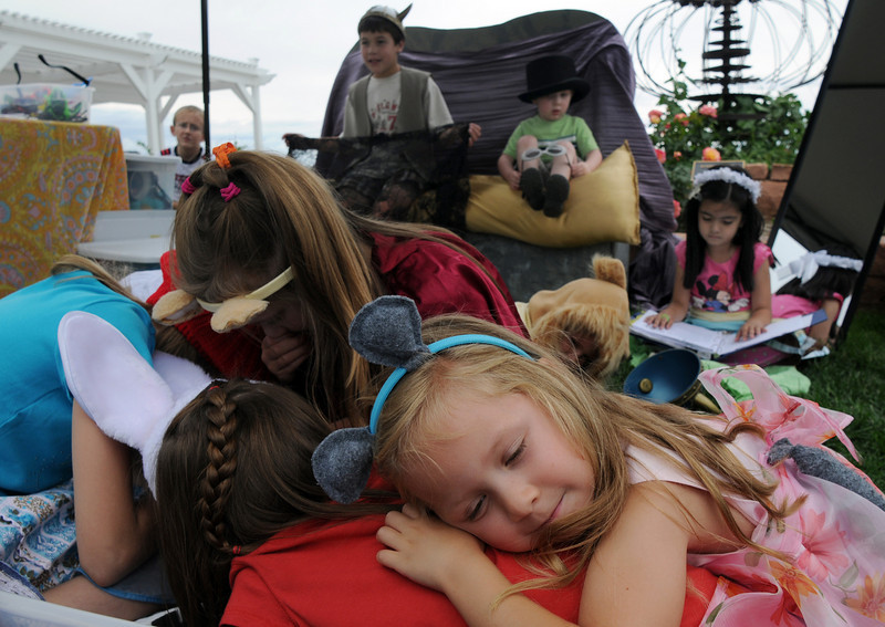 Ava Nordgren, 5, sleeps as a mouse during an improvisational play of the lion and the mouse at the Backstory Theater booth during the Broomfield Council on the Arts and Humanities Summer Sundays at the Brunner <br /> Farmhouse.<br /> <br /> July 11, 2010<br /> Staff photo/ David R. Jennings